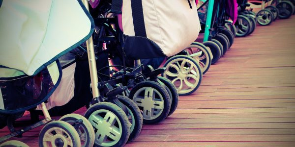 many strollers for toddlers parked on the parquet floor of wood